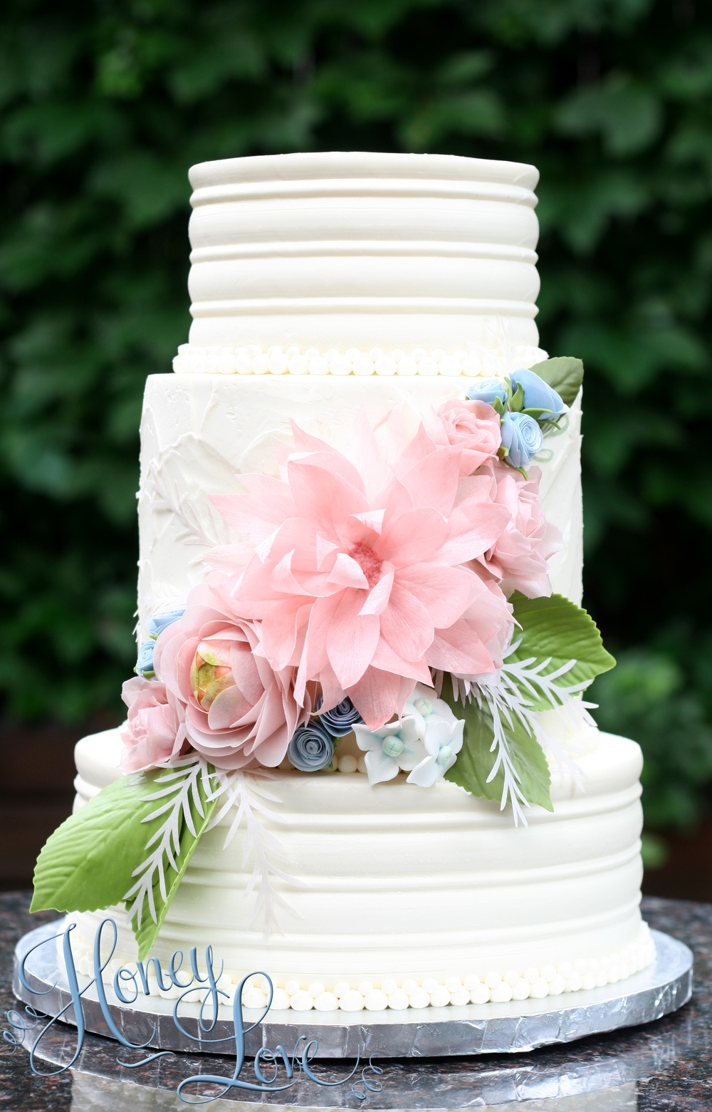 "Smooth buttercream covers this contemporary and classic wedding cake. Flower arrangement is a combination of handmade sugar and edible wafer paper details. Size: (3-tiers) 8"", 6"", 4"""