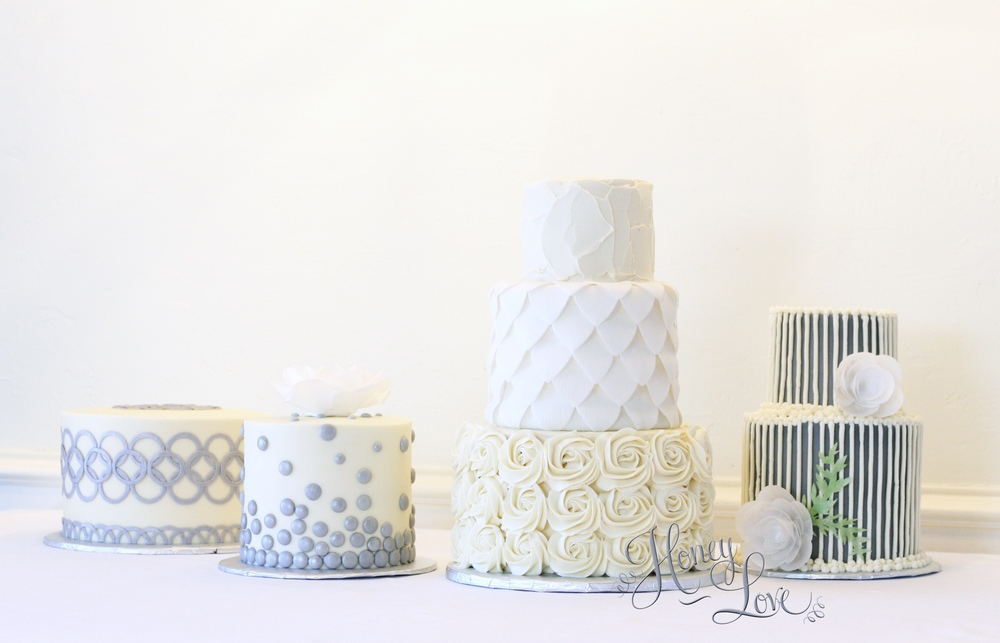 A multi-wedding cake arrangement creates interest and conversation. These cakes are iced with fresh buttercream and accented with fondant details and edible wafer paper flowers.