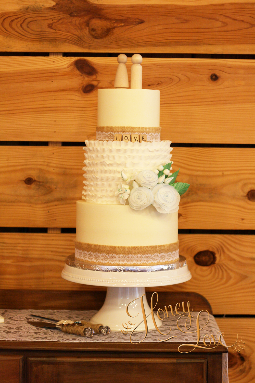 "A burlap and lace wedding cake with smooth buttercream, fondant ruffles, and edible wafer paper flowers. Size: 10"", 8"", 6"" with 3-layers per tier."