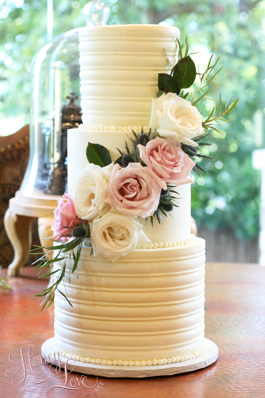 "A textured buttercream wedding cake with fresh flowers. 10"" 8"" 6"" with 3-layers per tier."