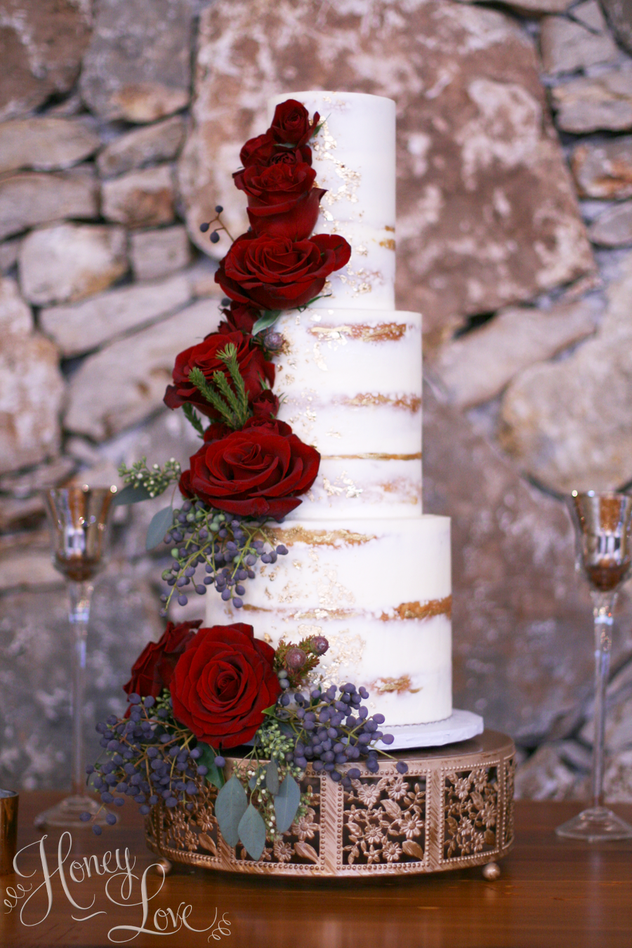 This semi-naked wedding cake is accented with fresh flowers and gold leaf details.