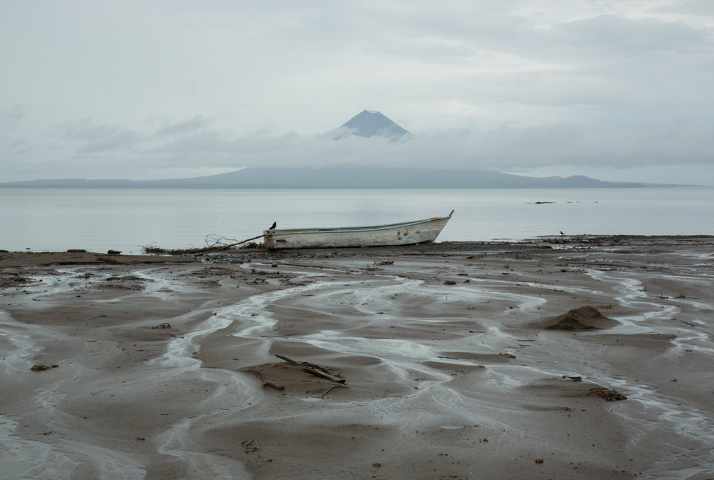 On the shores of Lake Nicaragua with the twin peaks of Ometepe Island in the distance near Rivas, Nicaragua