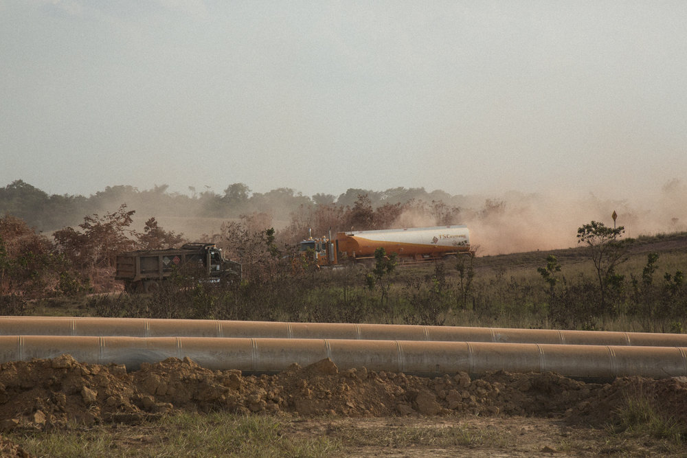 Trucks carrying Ecopetrol oil kick up thick dust through a landscape crisscrossed by pipes carrying oil and water. Locals complain that dust pollution has caused respiratory problems and pollution from noise has affected animals and humans alike. April 9, 2017. Vereda Rubiales, Meta, Colombia. April 9, 2017