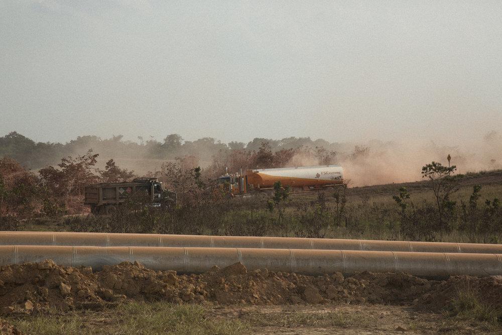 Camiones levantan un polvo grueso a través de un paisaje entrecruzado por las tuberías que llevan aceite y agua. Pobladores se quejan de que la contaminación del polvo ha causado problemas respiratorios y la contaminación por el ruido ha afectado tanto a animales como a seres humanos. 9 de abril de 2017 Rubiales, Meta, Colombia