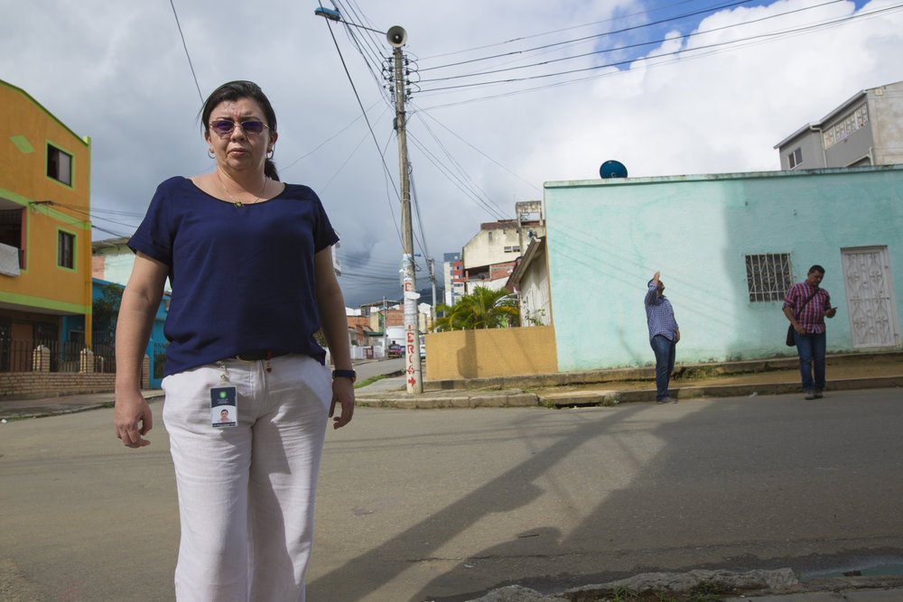 Julia Figueroa, human rights lawyer and leader of the CCALP, all women's legal collective, in the street outside her office. She has received multiple death threats in the street and has been followed, fearing for her life at times. She is now assigned two armed escorts, a bullet proof jacket and an armored truck for her protection, although she fears her very own escorts' ties to the military may put her at risk. Bucaramanga, Colombia. May 9, 2017.