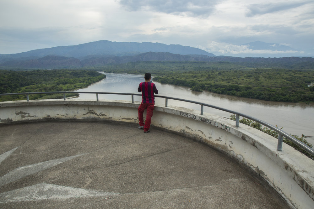 "A young man observes the Magdalena River a few kilometers after the Quimbo dam from a restaurant lookout. Writing on the wall says ""Forbidden to climb the wall."" Local fishermen say that according to the construction of the dam, the river no longer flows and has reduced the amount of fish to a level below what they can subsist on. March 19, 2017. Near the Jaguas, Huila, Colombia."