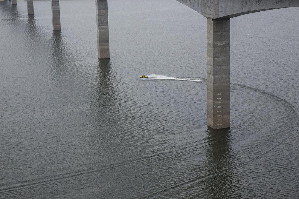 A jet ski passes under a recently constructed bridge running over the Quimbo dam reservoir that fills the Magdalena river valley near the town of Las Jaguas, Huila, Colombia. March 18, 2017