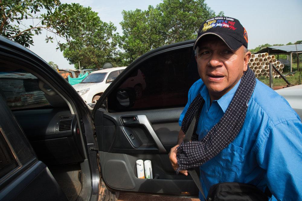 """Héctor Sánchez, líder comunitario de la vereda de Rubiales sale de su camioneta blindada, la cual le fue entregada por el estado Colombiano como parte de su Unidad Nacional de Protección. Héctor ha recibido varias amenazas de muerte de los """"Águilas Negras"""" y cree que las amenazas realmente provienen de fuerzas de seguridad de Ecopetrol que quieren intimidar a desalojar de su comunidad por su activismo. Lleva seis meses en su esquema de protección con carro blindado, dos guardaespaldas y un chaleco antibala. Rubiales, Meta, Colombia. 10 de abril, 2017"""
