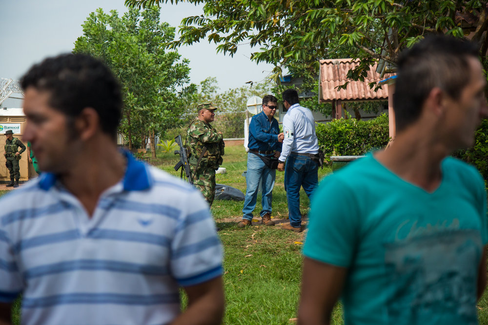 Two Ecopetrol employees shake hands while two local fishermen affected by oil pollution listen to a meeting between Ecopetrol and the community of Rubiales to ask permission to increase the amount of water used in the extraction of oil from rivers from 300,000 liters to 600,000 liters Liters per day. Human rights defenders claim links between oil companies and paramilitary groups. Rubiales, Meta, Colombia. April 8, 2017