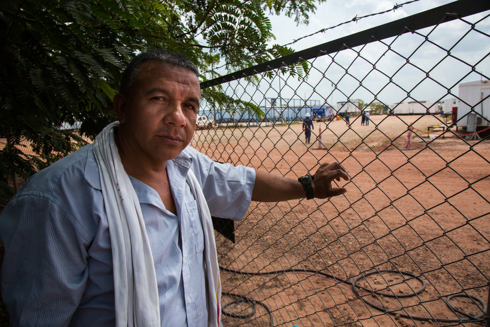 Héctor Sánchez stands along the fenceline of an Ecopetrol base in Rubiales, Meta where he is not allowed to enter. Rubiales, Meta, Colombia. April 9, 2017
