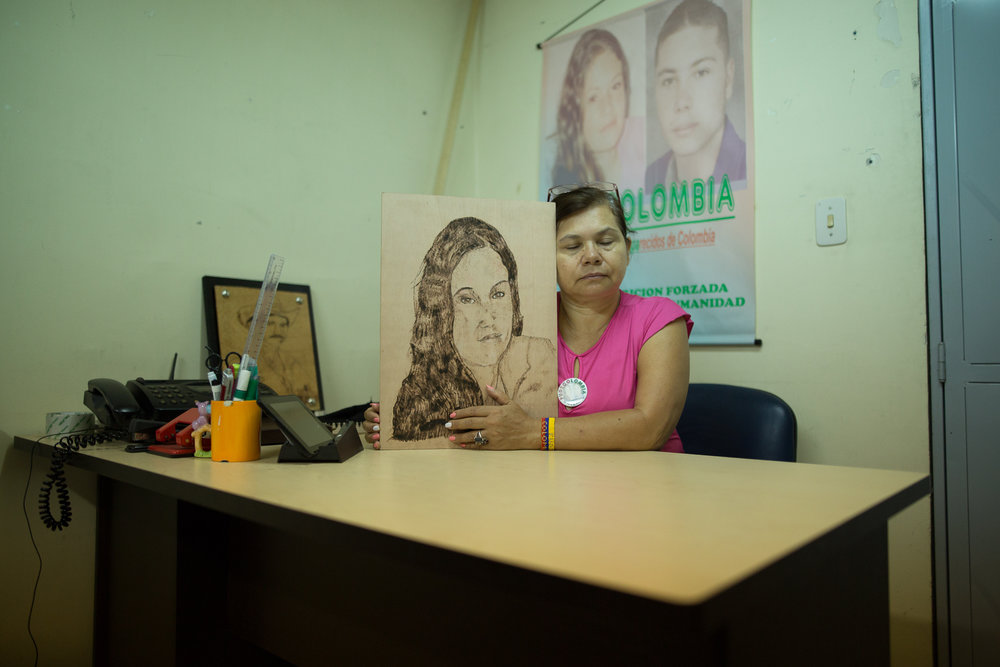 Imelda Olivia Martinez Reyes, 56, sits with a portrait of her daughter who was disappeared in 2004 at the age of 16 years old. Her son was also disappeared, presumably by paramilitaries, for her involvement in the Union Patriotica. She formed FUDECOLOMBIA, an organization working for disappearance victims' rights in the department of Santander. She still does not know what ever happened to her children. Bucaramanga, Colombia. May 9, 2017.