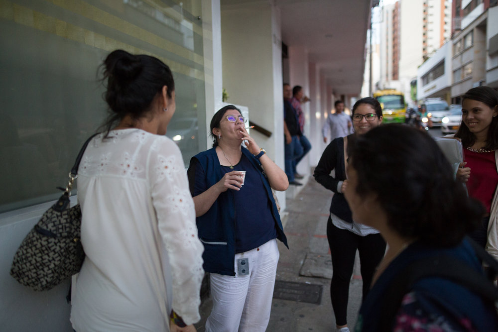 Julia Figueroa smokes a cigarette outside of a meeting while talking with her younger colleagues in Bucaramanga, Santander, Colombia. May 9, 2017.