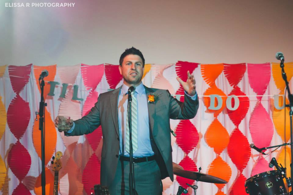 Just a shot above of my brother, the groom, giving at toast in front of the backdrop. Just a little brag. No shame in that game!  Photography by  Elissa R Photography