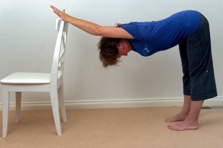 "Thoracic Stretch / Chair or Wall:  Place both hands on the top of a chair or wall. Keeping your legs straight but knees relaxed, slowly back up until arms are fully stretched (if your elbows are bending using a chair or bench - then use the wall and bring your arms up higher). Slowly drop your chest toward the floor and gently lift our tailbone. Or you might prefer the alternative way of saying that ""push your butt back!"" Relax your head."