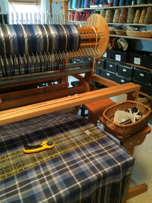 The back of the loom, with finished cloth coming up from the front of the loom.