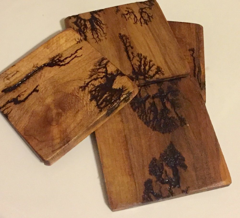 Hardwood coasters with electro-burning designs.  There are no two alike.