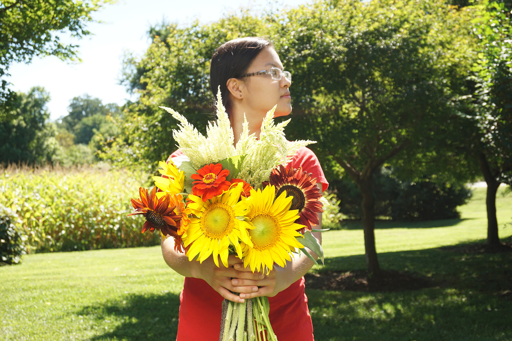 My new friend Angela holding a big old bouquet of sunflowers, zinnias, and celosia.