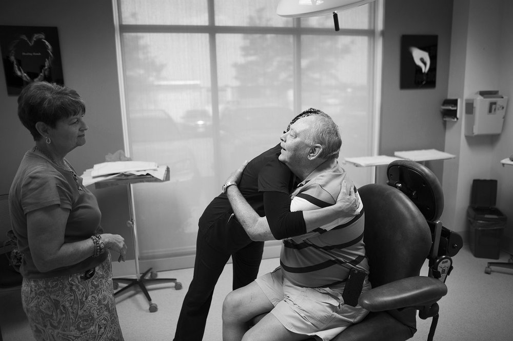 Vielka D. Inman the surgical manager at Virginia Dermatology and Skin Cancer Center hugs David Wright Jr. after David's skin cancer surgery on his hand, David's wife Lou Ann Wright stands to the left.