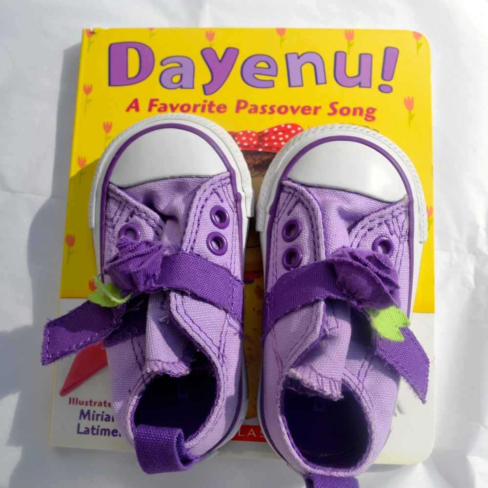 """Dayenu"" book  purchased at  Park Slope Community Bookstore . Pastel purple baby Converse Chuck Taylors, ""vintage"" from  Lulu's Then and Now . Similar option  here ."