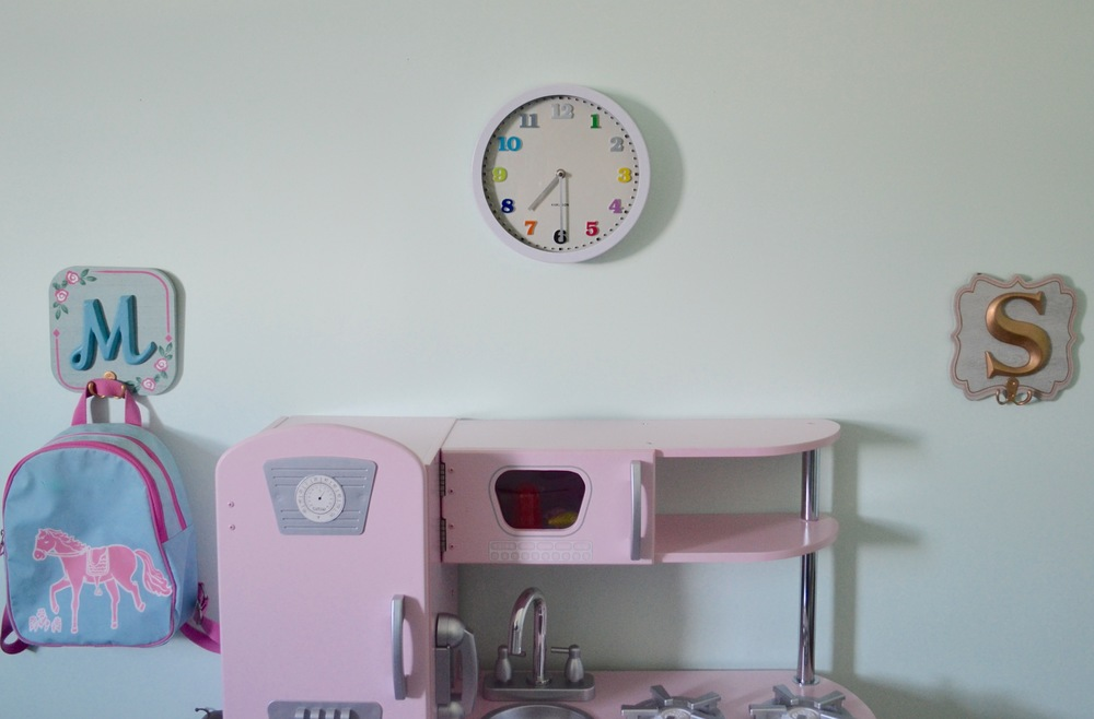 Initialed wall plaques with hooks hung at Tiny Human height are perfect for Client M to hang up her backpack after a tough day at the park. She can cook herself up something tasty in her fabulous pink play kitchen, while keeping an eye on the time.