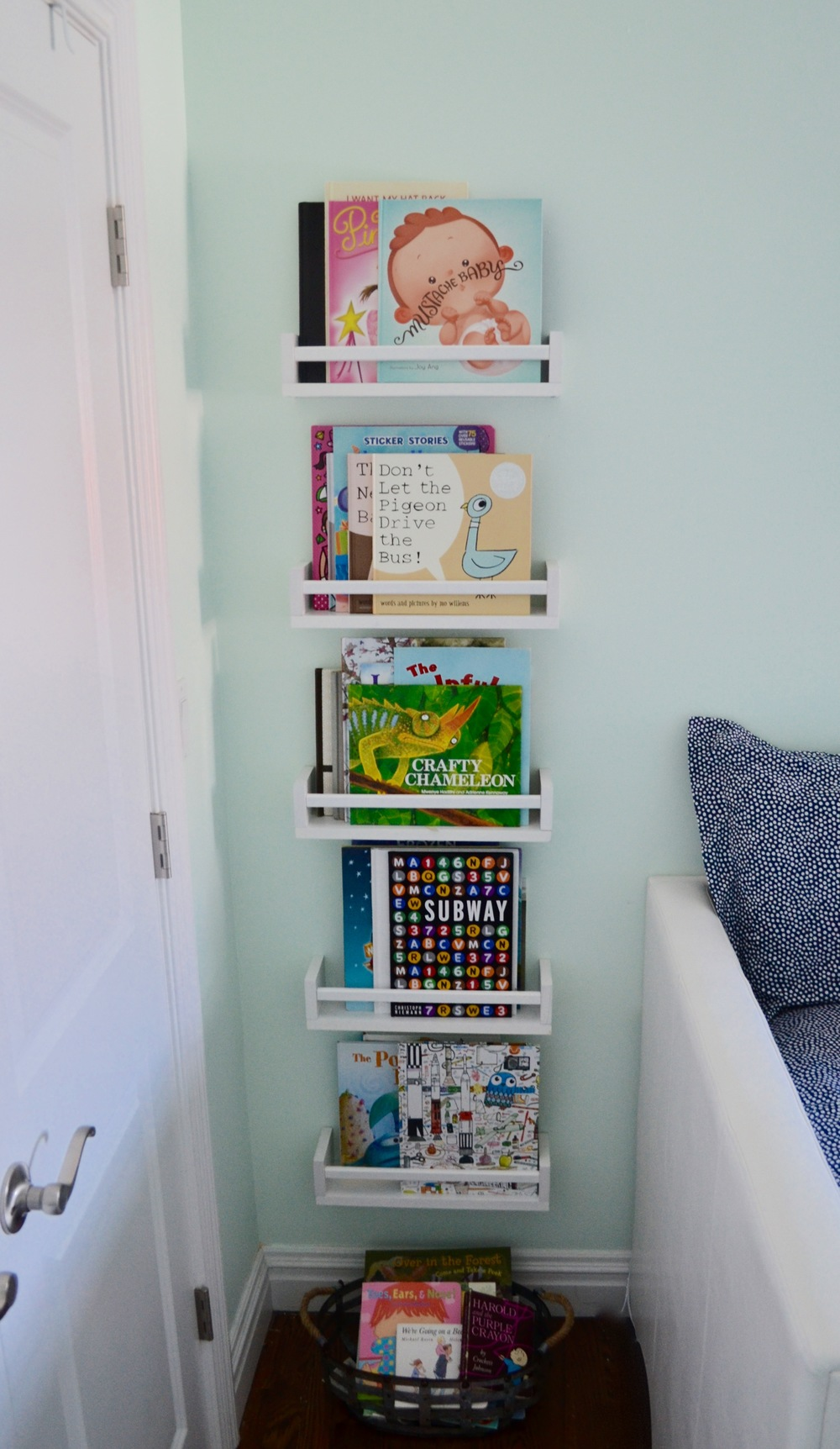 Client M is quite the little bookworm, so book storage was a priority. Wall-mounted shelves, bins and baskets for overflow did the trick.