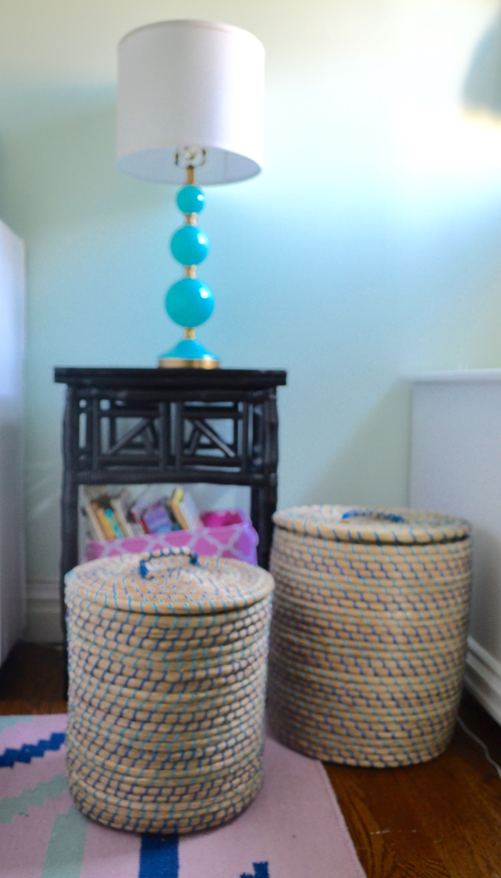 A nightstand houses a canvas bin full of books, and Moroccan style storage baskets with lids corral Client M's extensive stuffed animal collection.