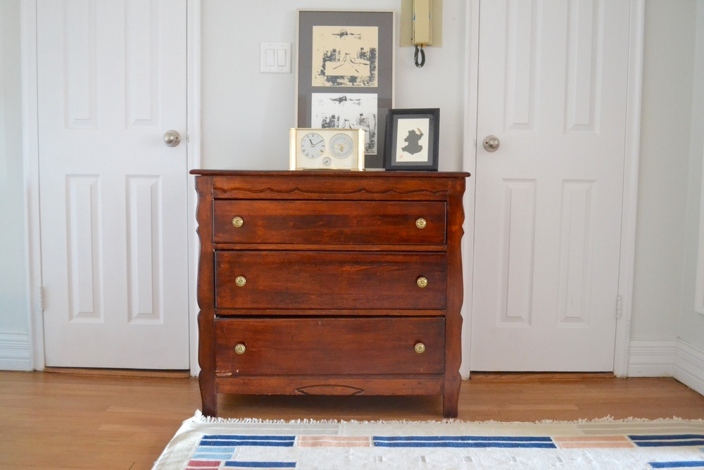 A previous bedroom dresser turned hall chest, topped with art collected by the couple is the perfect storage-providing accent.