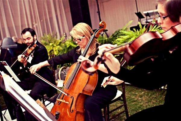 Sam Lester (right),violist, plays along with Annie (center), cellist, and Joe Lester (left), violinist, at a wedding ceremony in the country.