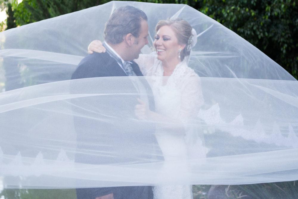 couple under the brides veil having fun