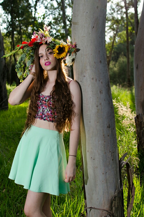 pretty hipster girl in the nature with crown of flowers