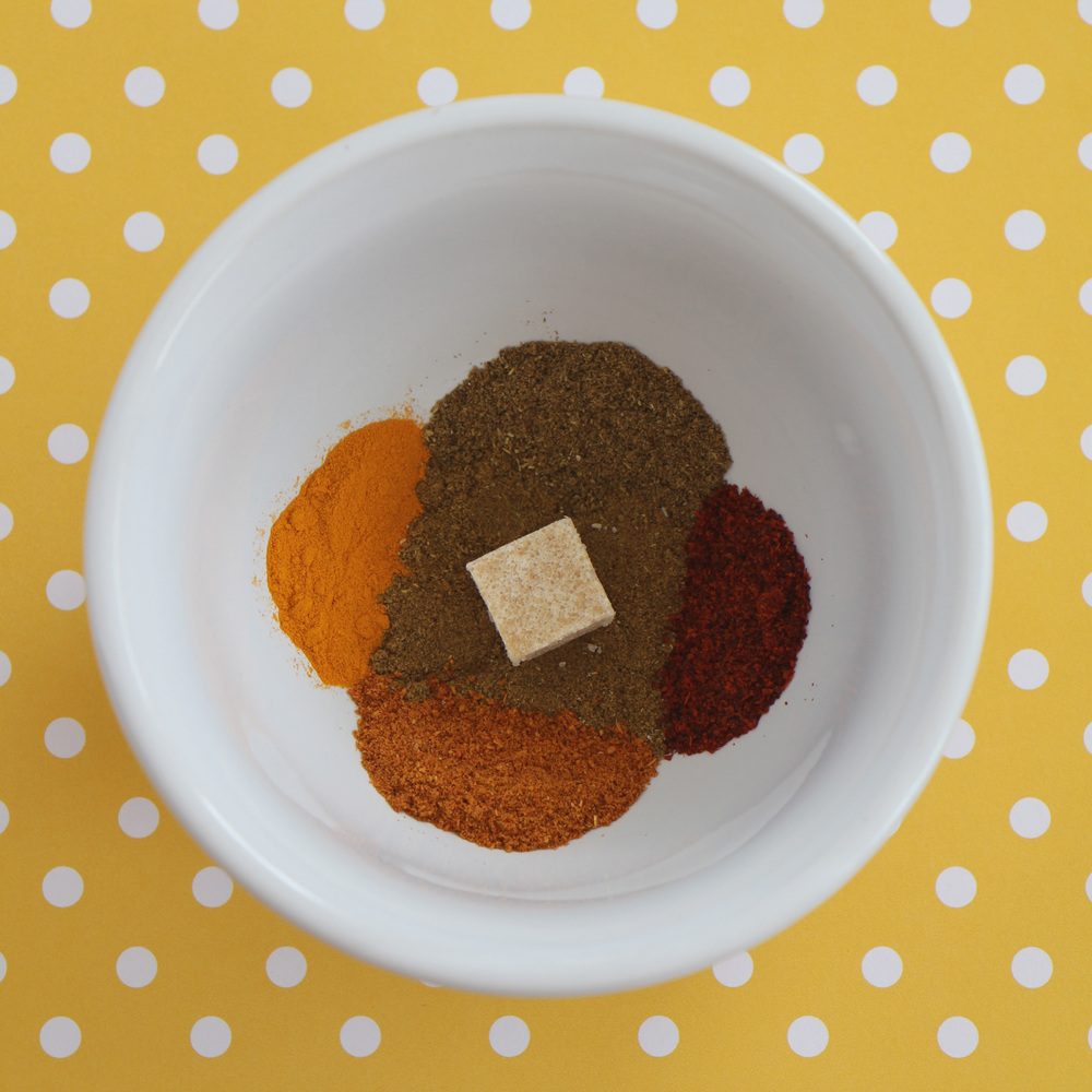 Clockwise from the top: garam masala, red chili powder, pav bhaji masala, turmeric. Center: cumin powder, garlic powder.