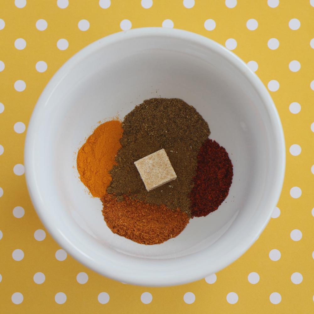 Clockwise from the top: garam masala, red chili powder, pav bhaji masala, turmeric. Center: cumin powder, garlic powder.