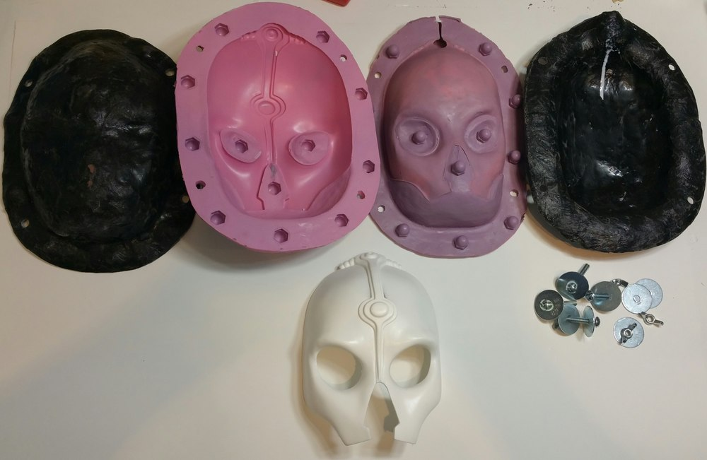 Black pieces are the mother mold (outter rigid shell) the pink/purple are the 2 piece mold, and the white face is Nihilus - the first pull.