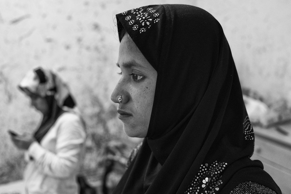 Laila Begum, 28, sits in her new apartment in Chicago.  In 2013, she fled her village in the middle of the night, boarding a small fishing boat on the river, as word of an imminent government-led attack spread.  She left behind her parents.  Her father would not survive.