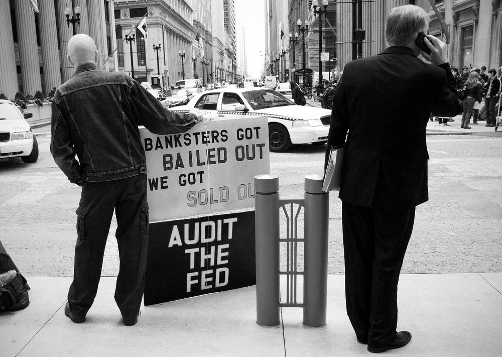 An Occupy Wall Street protestor and a business man exiting the Board of Trade share the space for a moment on October 14, 2011 in Chicago, IL.