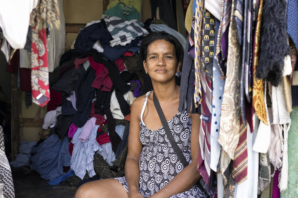 A woman sits among the clothes and ties in her store.