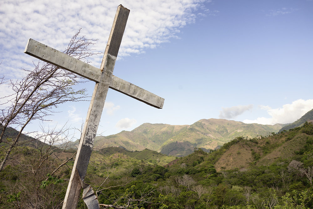 A wooden cross stands on top of a small mountain, overlooking the town and valley.