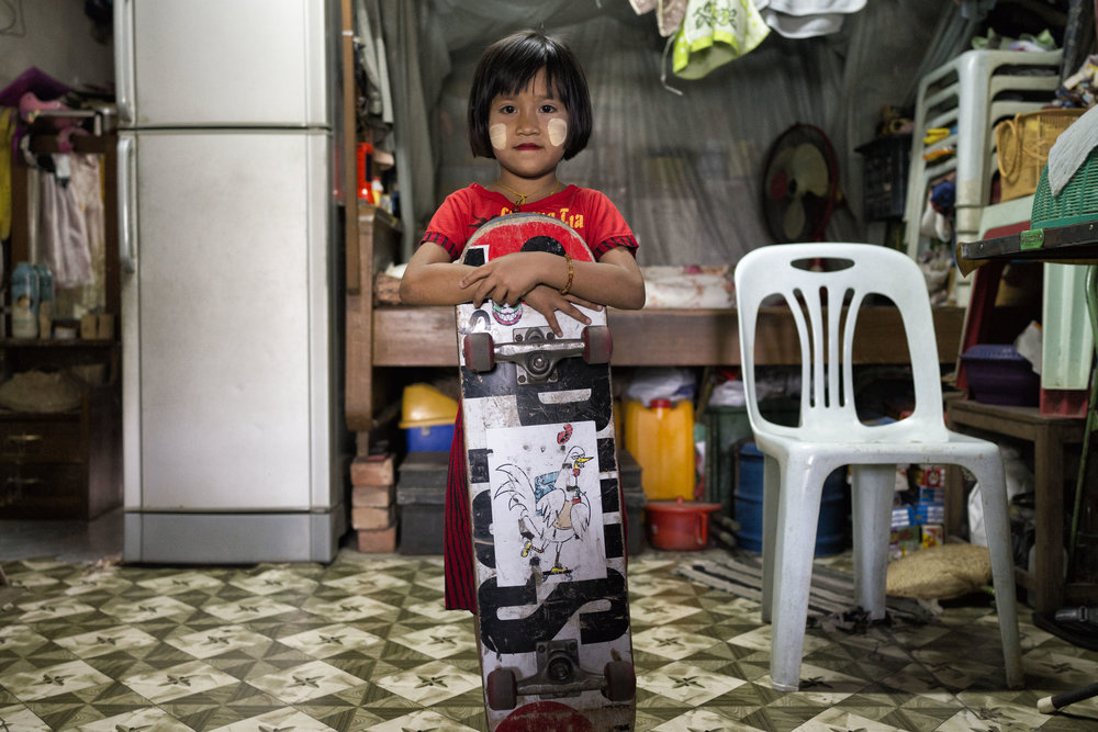 Aye, seven years old, stands in the home she shares with her grandparents, father and extended family. They also rent the apartment next-door.