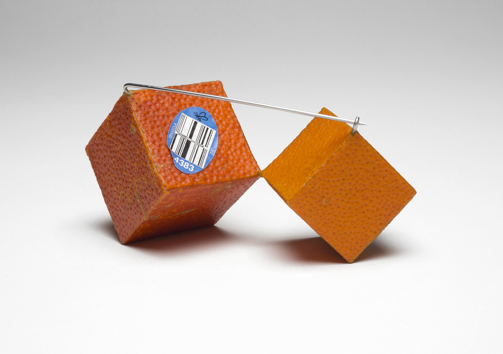 "Cubic Tangelo Brooch  (pin back detail), 2015. Tangelo peel, plywood, steel. 2"" x 3.75"" x 2"""