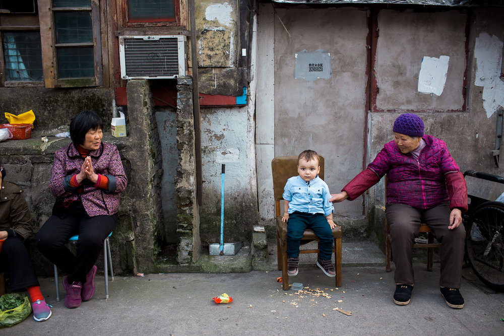 An unconventional family photography portrait of a young boy with two elderly ladies in a back street in Shanghai by Kuala Lumpur Based photographer Erica Knecht