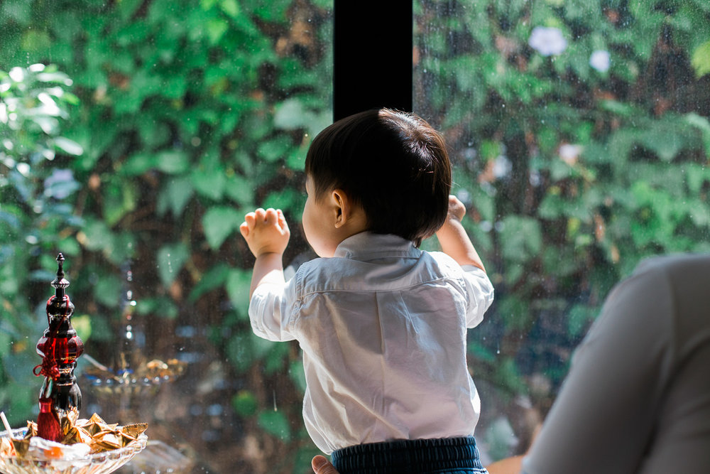 A little boy looks out a window during a family photoshoot in Kuala Lumpur.