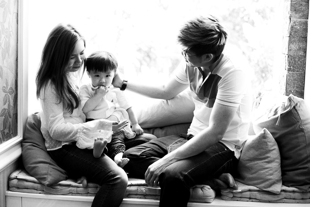 A black and white image of a mother, a father, and their toddler boy in a window seat by kuala lumpur based photographer Erica Knecht