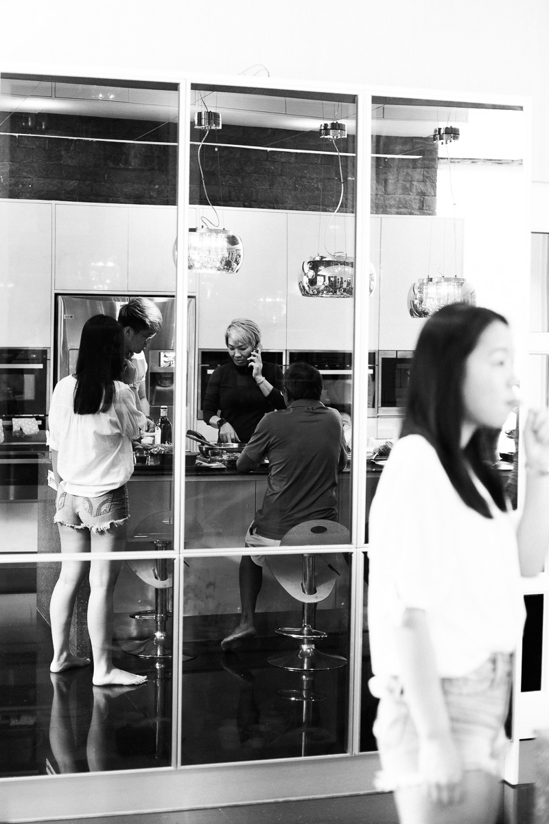 A documentary style images in black and white showing a large family gathering around a kitchen island at home in Kuala Lumpur.