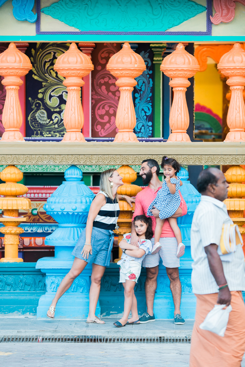 A family stands in front of a temple as a worshiper walks by at Batu Caves in Kuala Lumpur.