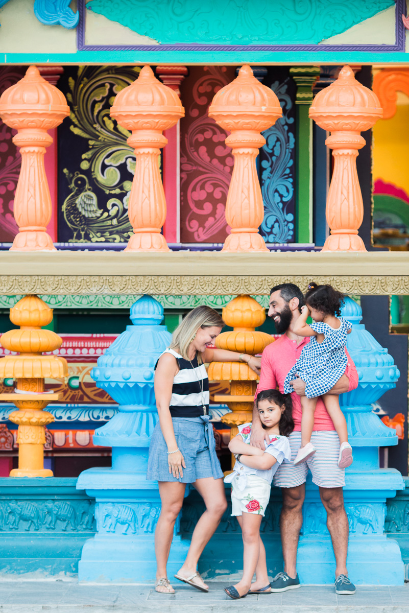 A family with two little girls in front of a temple at Batu Caves.