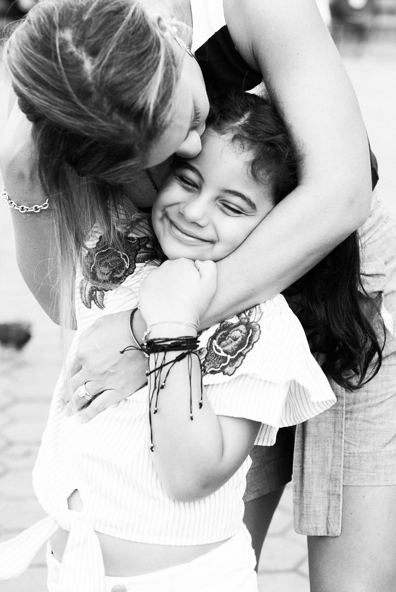 A black and white image of a mother embracing her smiling daughter in Kuala Lumpur by family photographer Erica Knecht.