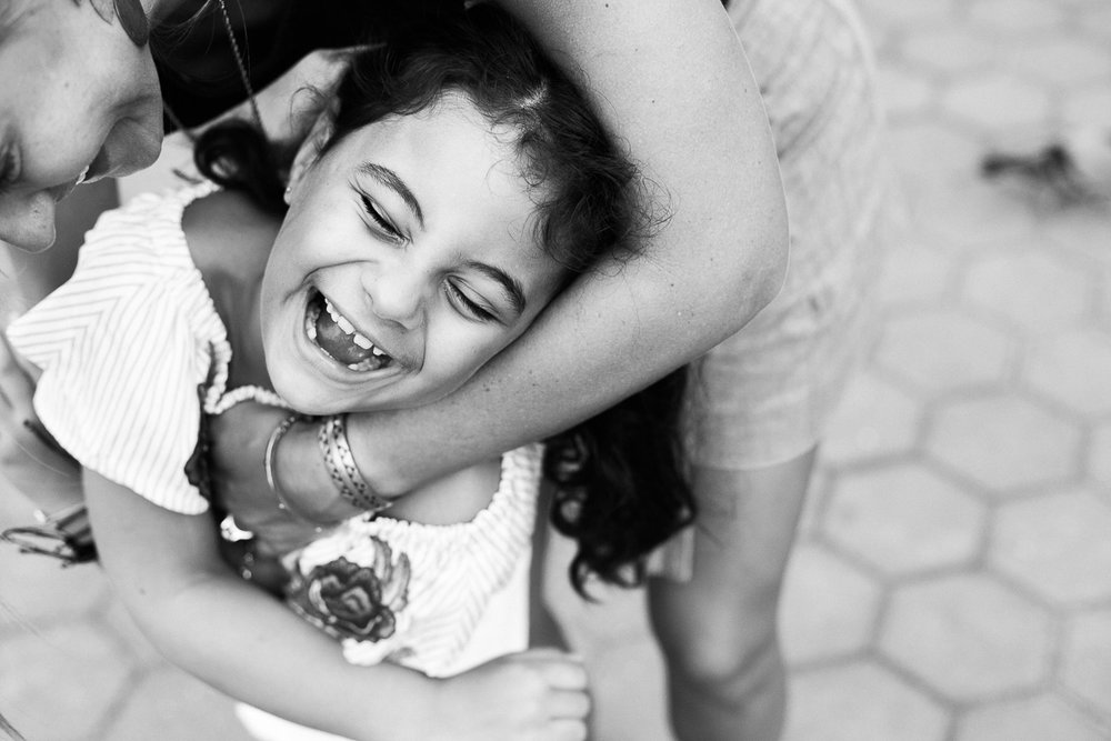 A black and white image of a mother tickling her daughter by family photographer Erica Knecht in Kuala Lumpur.