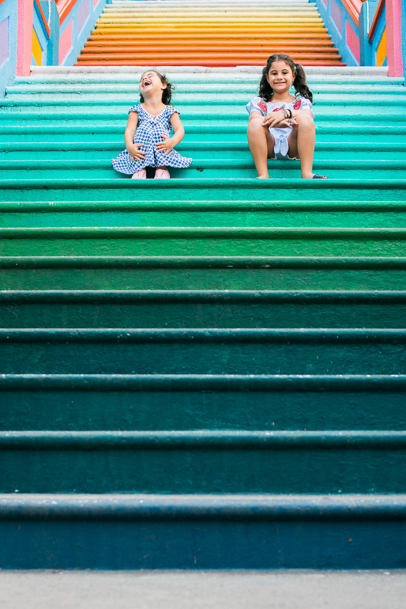 Two little girls laugh on the colourful steps of Batu Caves.