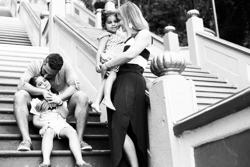 A black and white family portrait with a mother and father each embracing a daughter in Kuala Lumpur by Erica Knecht.