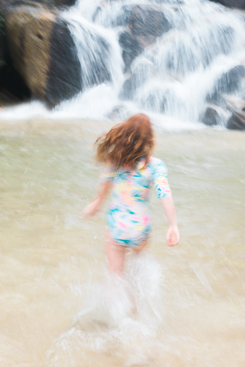 a girl runs out towards Sungai Pandan waterfall near kuantan by erica knecht, a kuala lumpur based family photographer